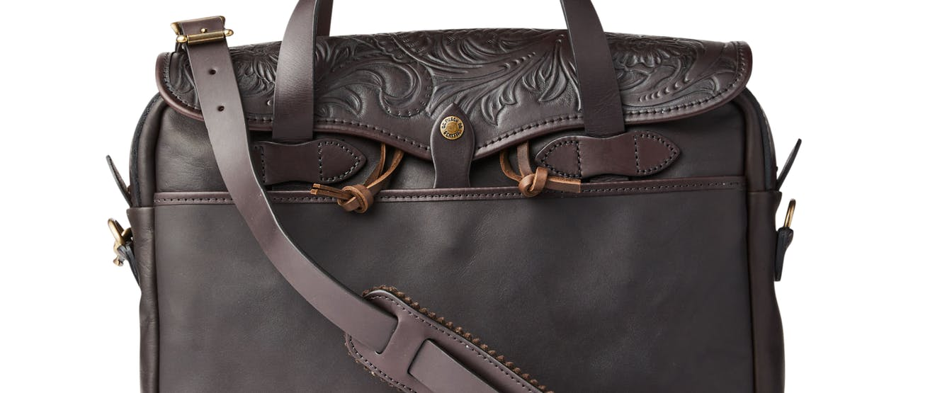 a dark brown leather brief case style bag with floral designs on the upper flap