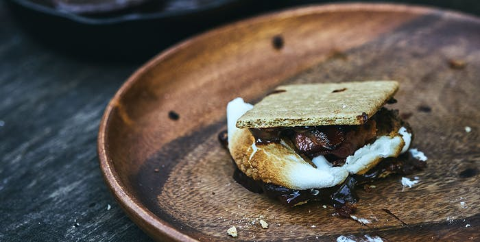 smore with bacon on a wooden plate
