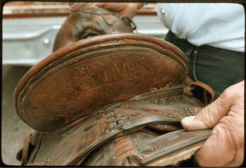 hands holding a hand-tooled leather saddle with letters and floral patterns carved into it
