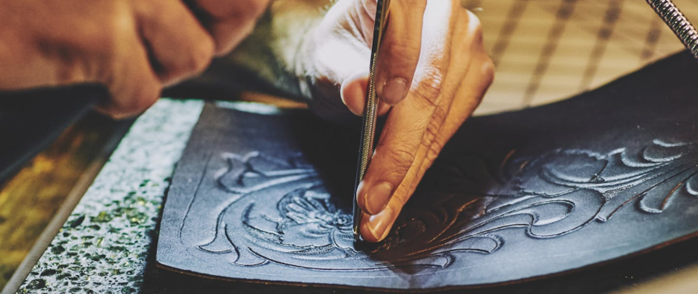 hand holding a silver tool and a black tool working on creating a floral design on a piece of dark leather