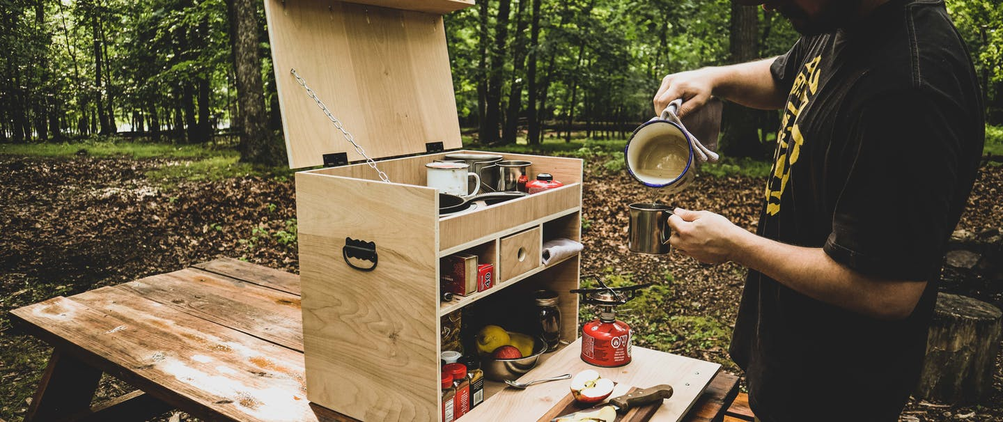 man pouring water into a measuring cup from a camp travel cooking supply box