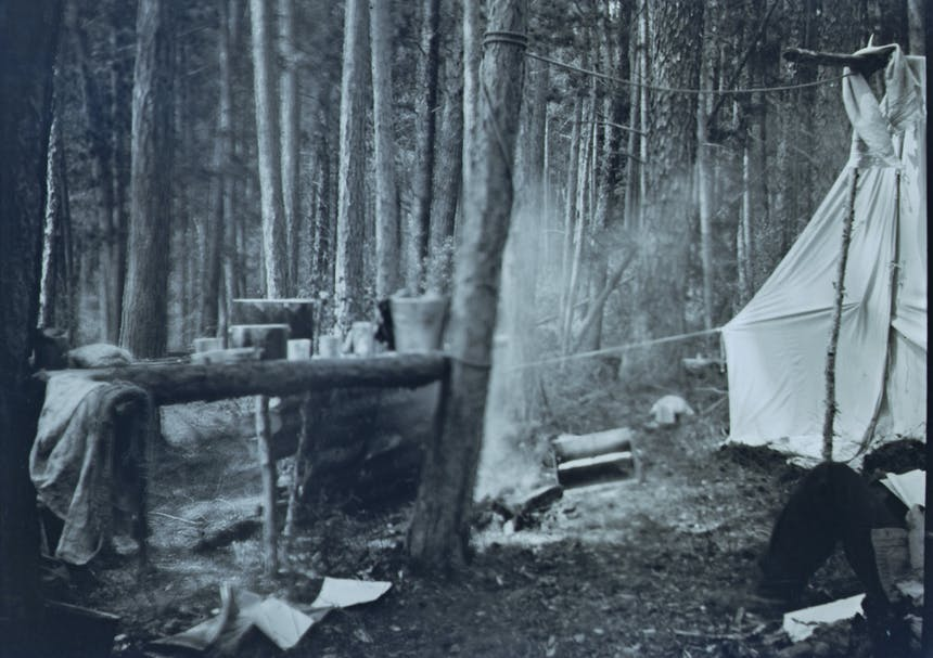 black and white image of a campsite with a large white tent and kitchen implements and firepit next to the tent
