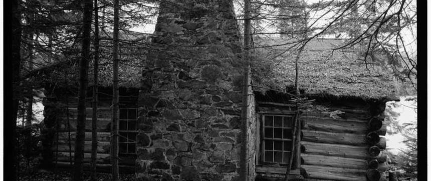 black and white image of a log cabin with a large central stone chimney