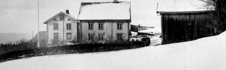 black and white image of two old white washed house structures and a dark barn in a snowy field