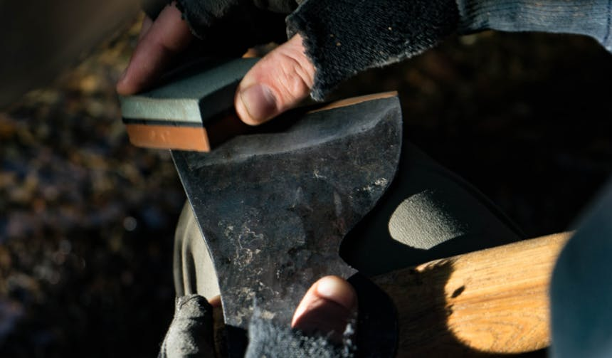 hand using a whet stone to hone an axe
