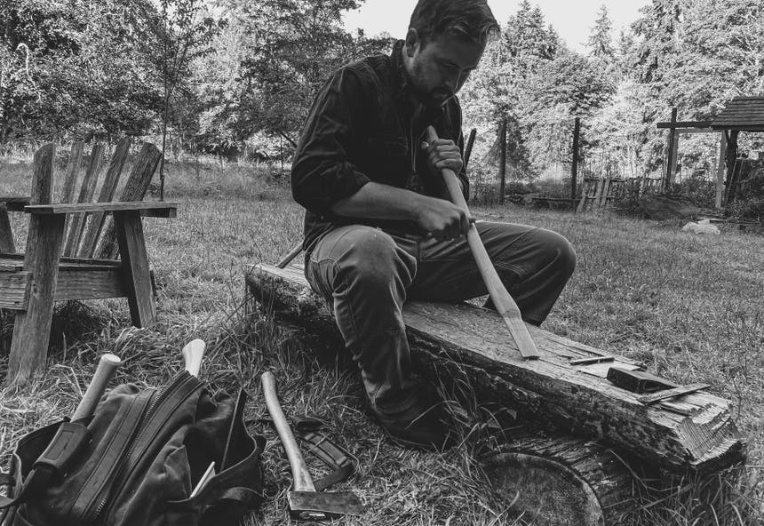 man working on sanding an axe handle while sitting on a log in an meadow