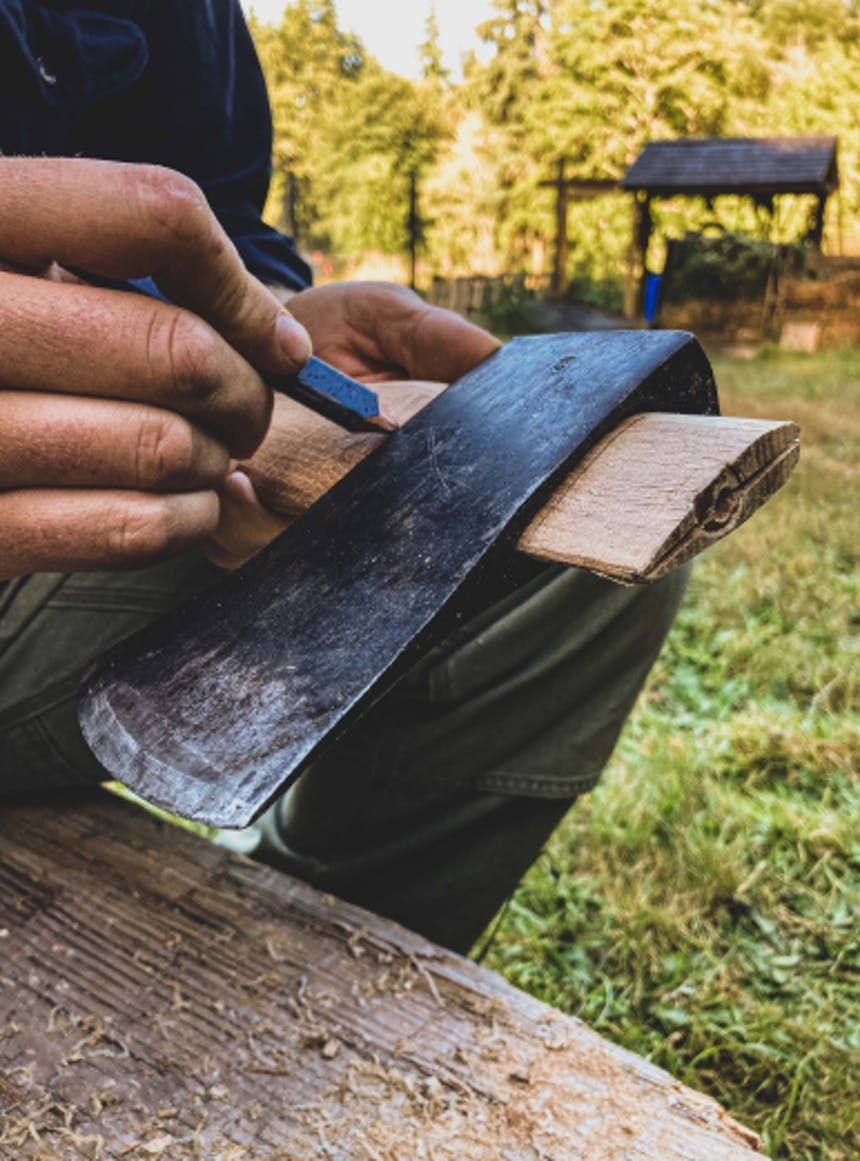 person drawing on an axe handle underneath the axe head in a grassy meadow