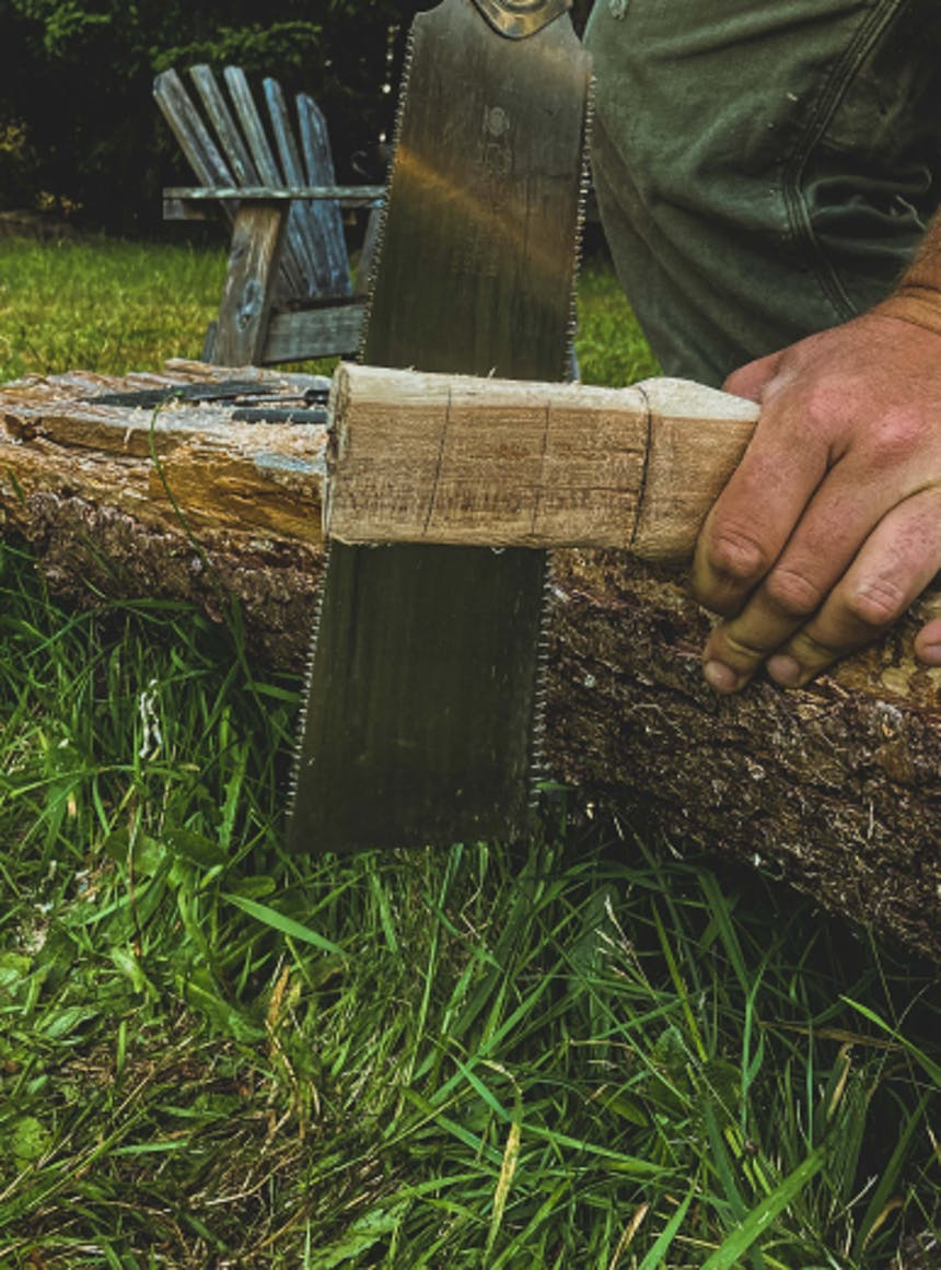 hand using a saw to cut down the side of an axe handle