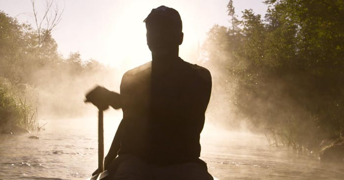 silhouetted man paddling a canoe in a river