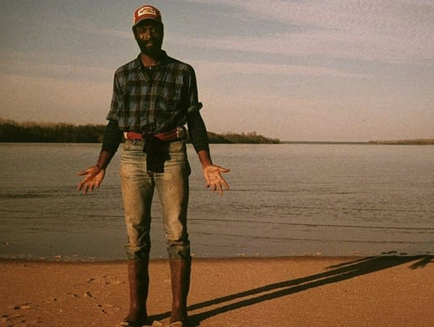 man in blue plaid shirt, waterproof boots standing on a beach at a lake