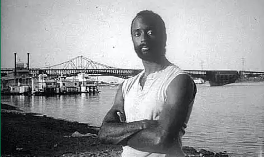 eddy harris standing on a beach in a tank top with an iron bridge and ships in the background