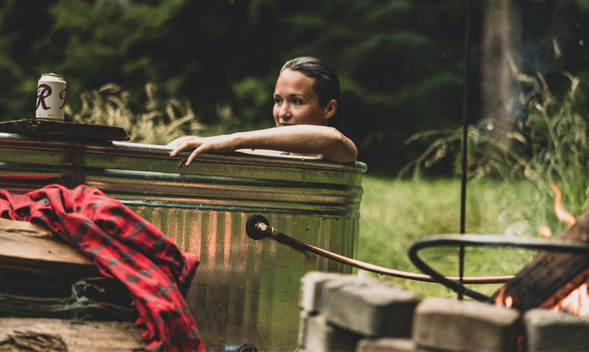 woman sitting in a homemade aluminum hottub in a meadow