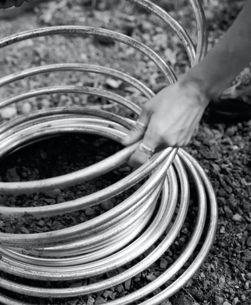 black and white image of hand holding a large coil of silver metal tubing