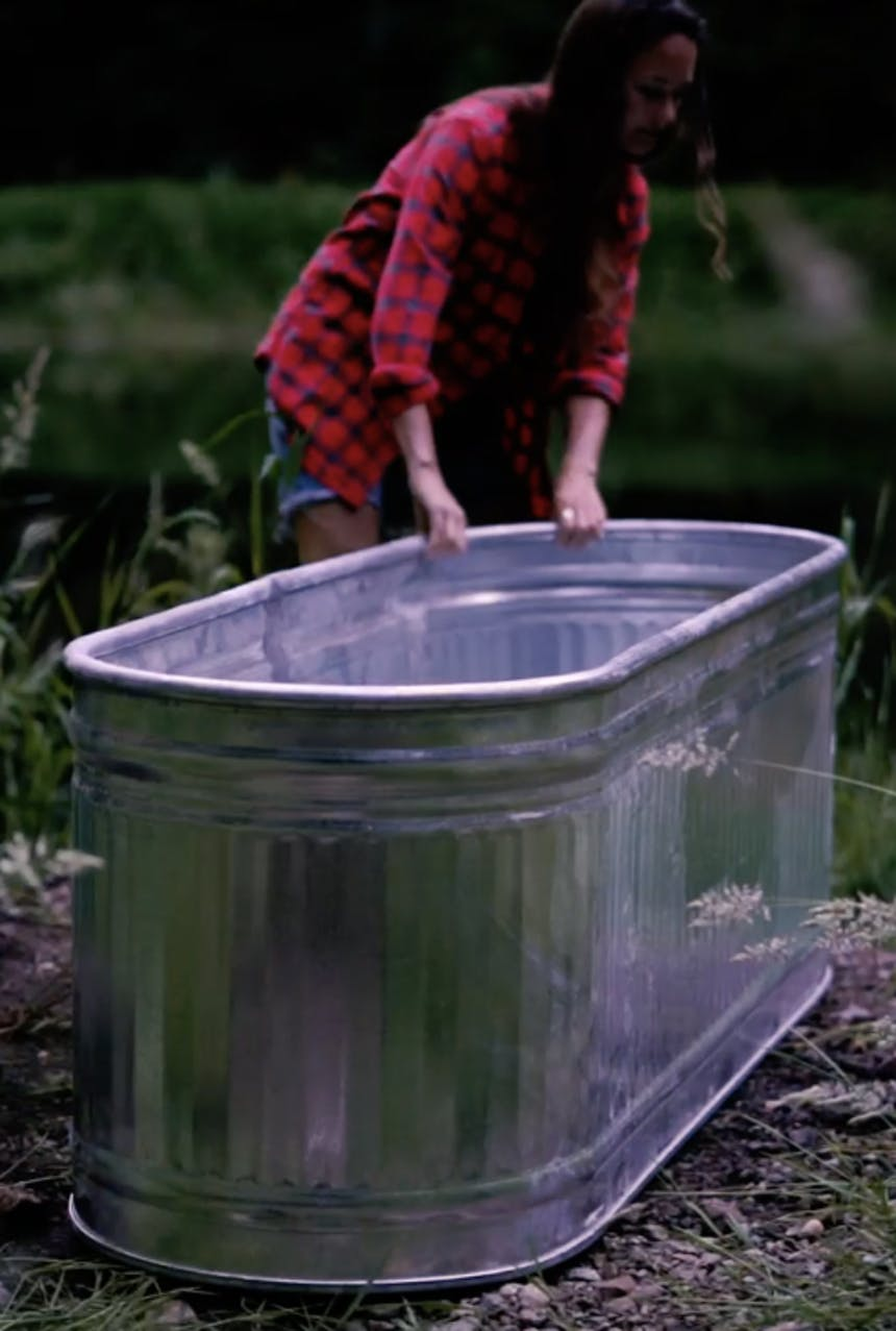 person in red and black flannel shirt with hands on a large metal tub in an outdoor area