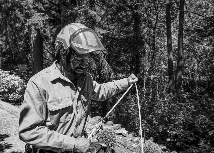 man holding a rope attached to his harness wearing a helmet with a face shield in a forest
