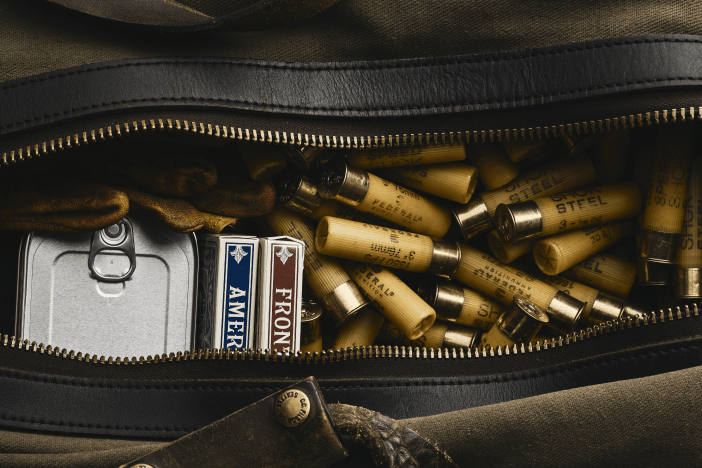 a filson duffel bag with packs of cards and shotgun shells in it