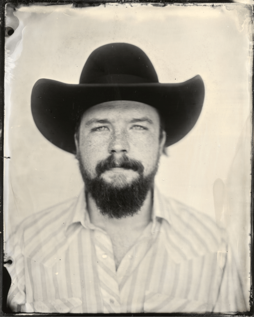 black and white portrait of man in black cowboy hat with beard