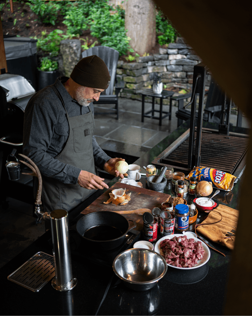man in beanie and overalls holding an onion by his setup for cooking venison chili in a kitchen