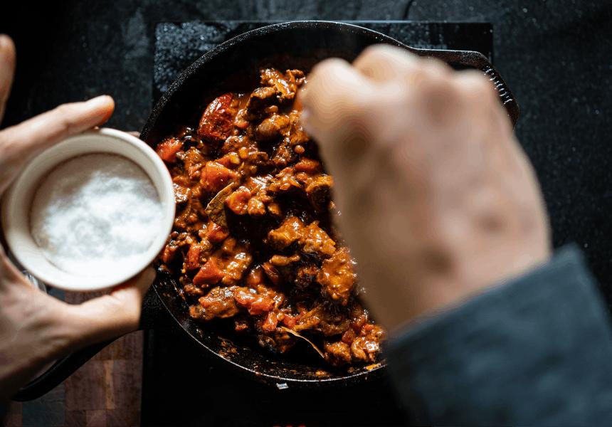 hand sprinkling salt into a cast iron skillet of venison chili