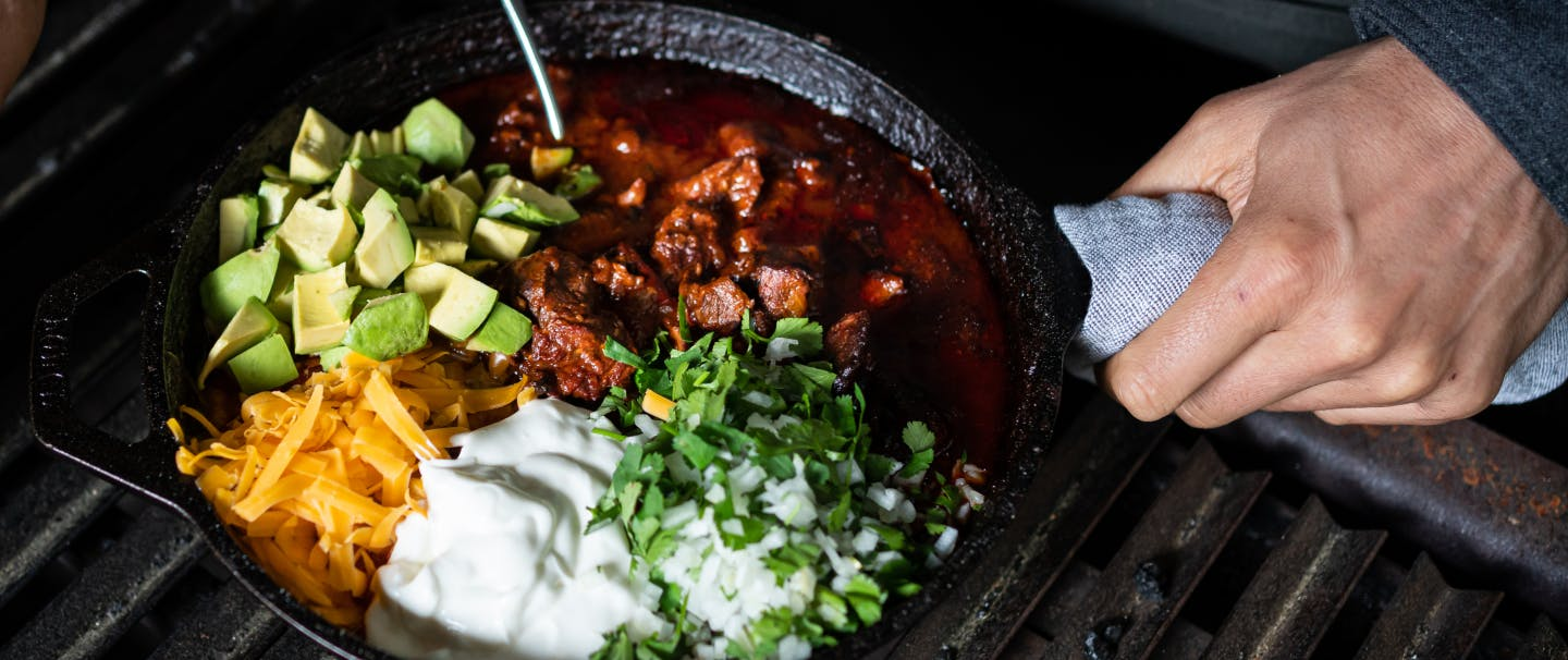 venison chili, cheese, avocado, sour cream, onion and herbs in a cast iron skillet on a grill grate