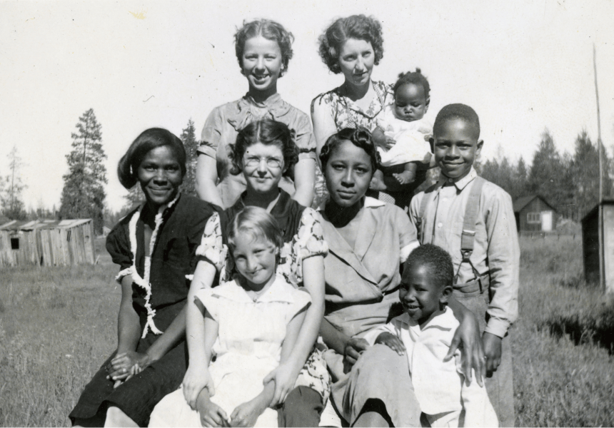 black and white image of a group of women and children standing in a field with a number of small structures spaced far apart from one another