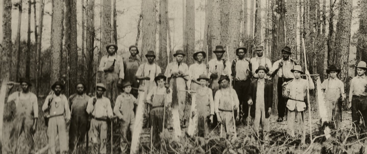 group of loggers in white shirts and overalls standing in forest