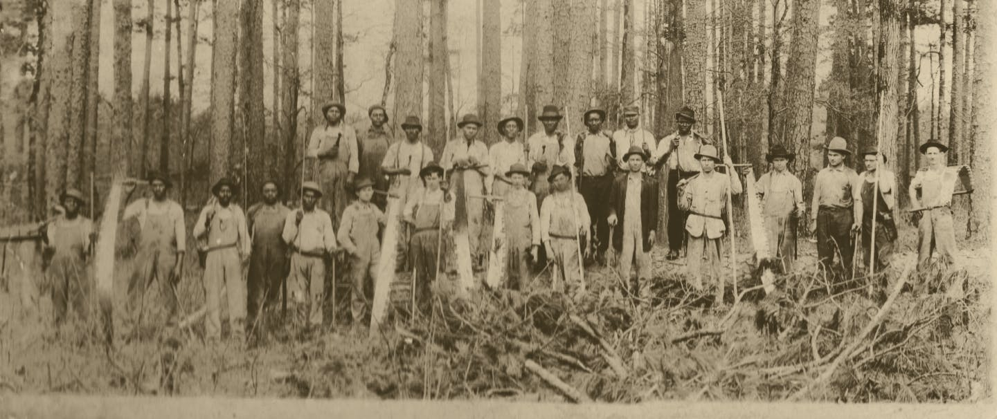 old black and white image of a large group of young men in hats and buttondown shirts and slacks standing in a pine forest