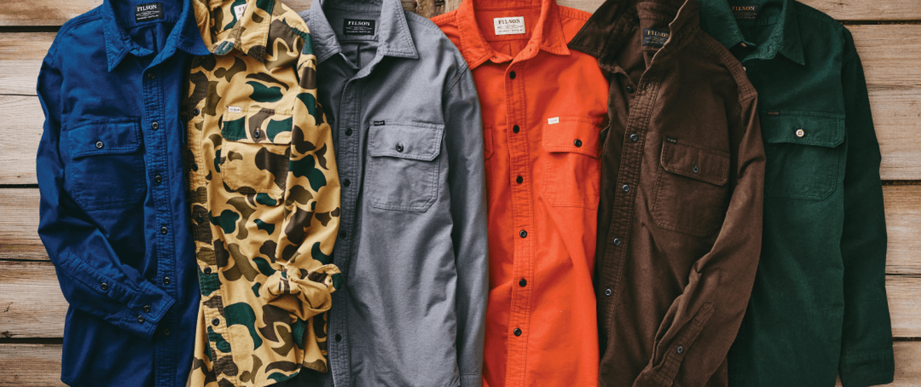 a collection of five filson shirts lying on a wooden surface