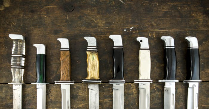 a collection of fixed blade buck knives on a table, detailing the handle materials