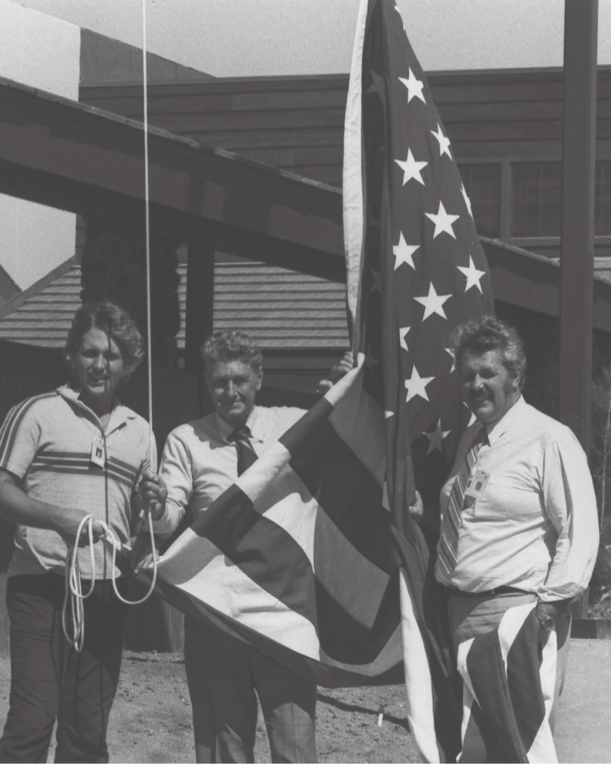 three people in a yard holding the american flag tied up on a flag pole