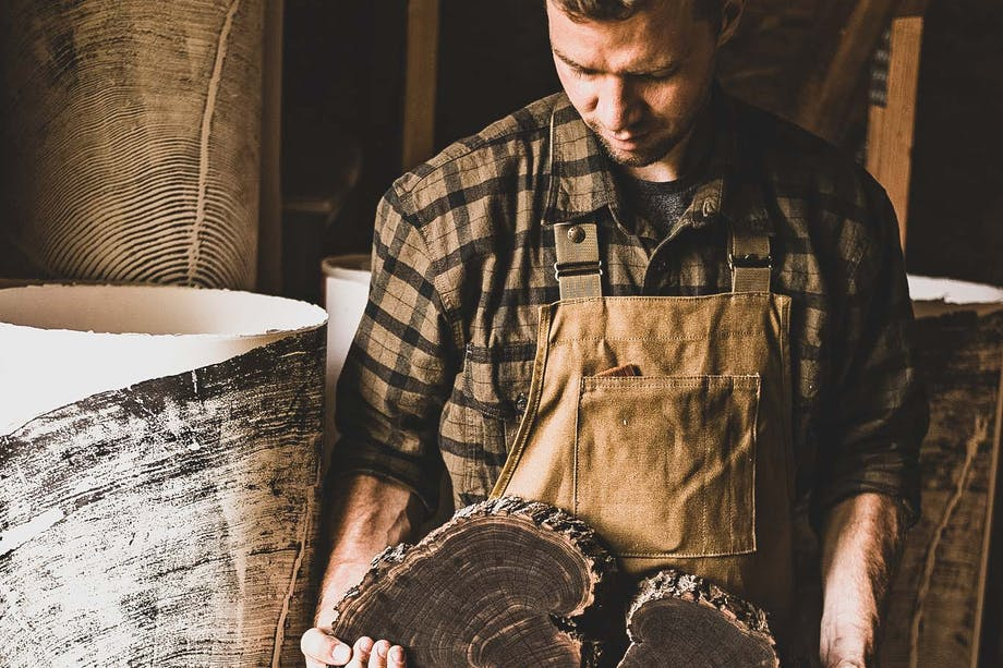 erik linton holding a large circular section of tree trunk that has been covered in black ink