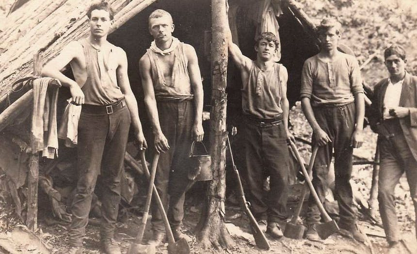 five young loggers standing in front of a handmade wooden shelter holding axes