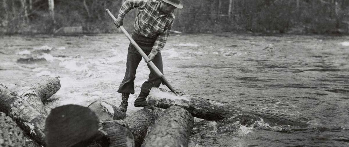 logger using a tool to manipulate a log in a river