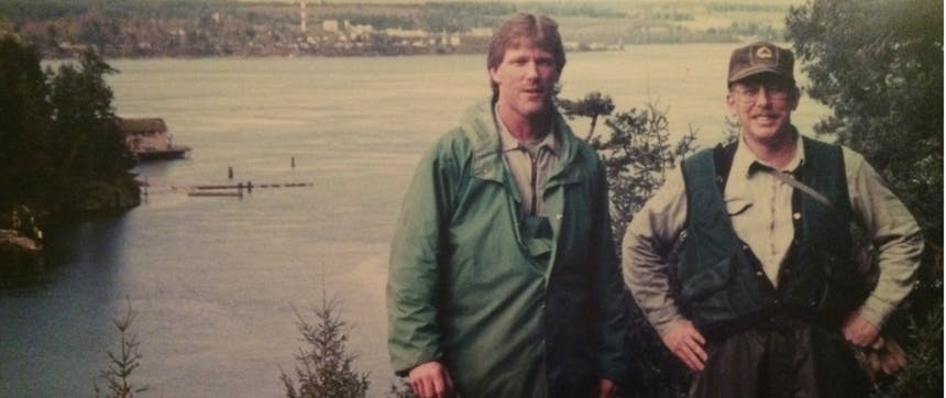 two men standing in the woods overlooking a large body of water