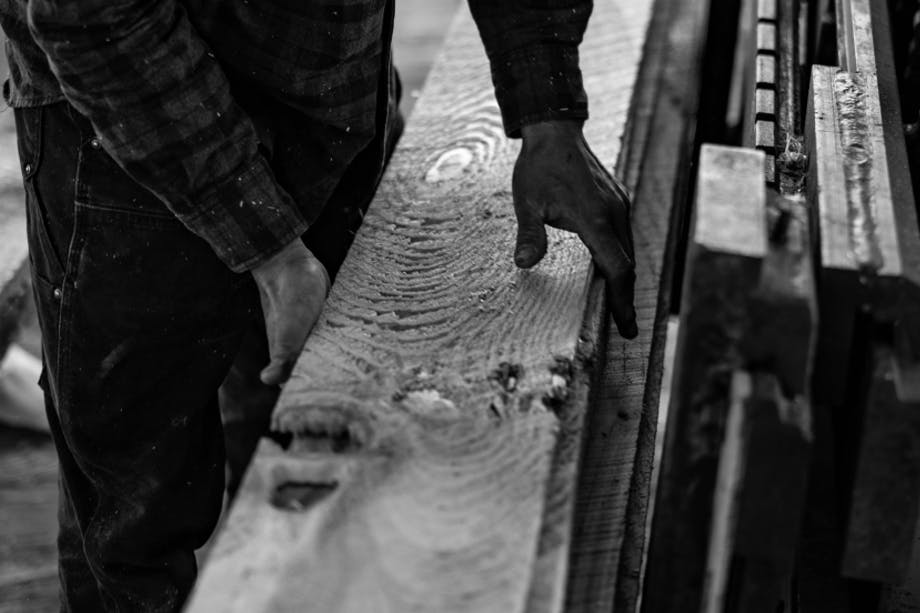 hands holding a long freshly milled board