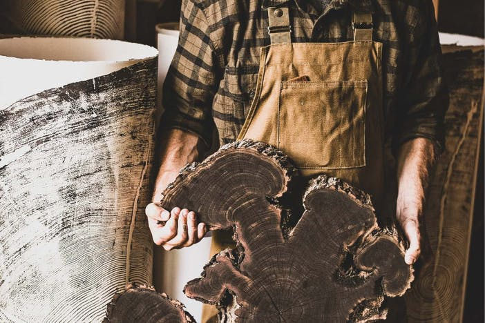 man holding gnarled and bulbous shaped cross-section of tree trunk