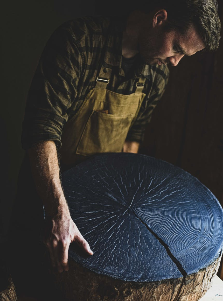 man holding a large circular section of tree trunk that has been covered in black ink