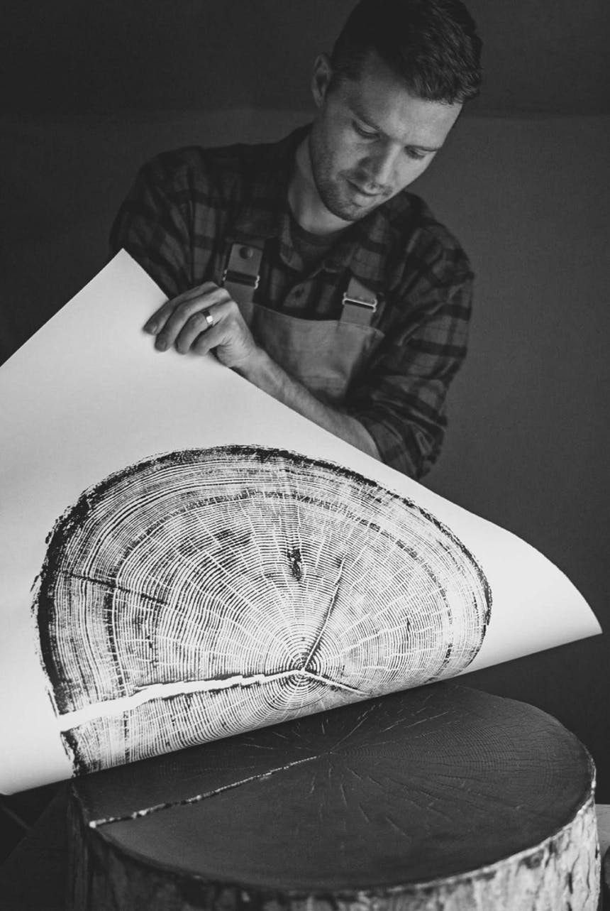 person pulling an ink pressing on a large sheet of paper off of a tree trunk