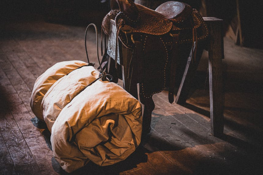a canvas bedroll lashed with rope sitting next to a saddle on a saddlehorse