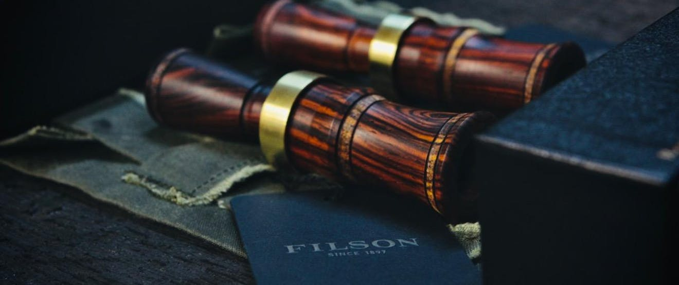 wooden duck calls with brass ring and filson card next to the calls