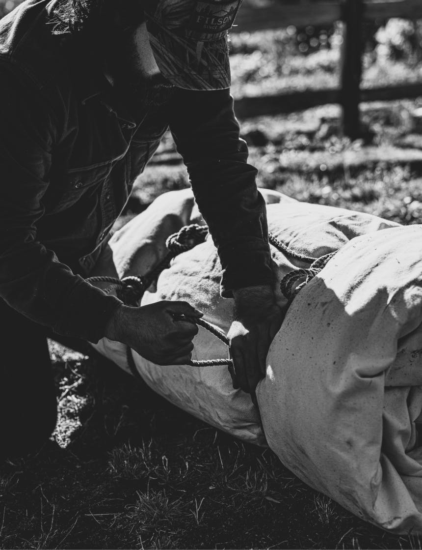 person tying a canvas bedroll with rope in a field