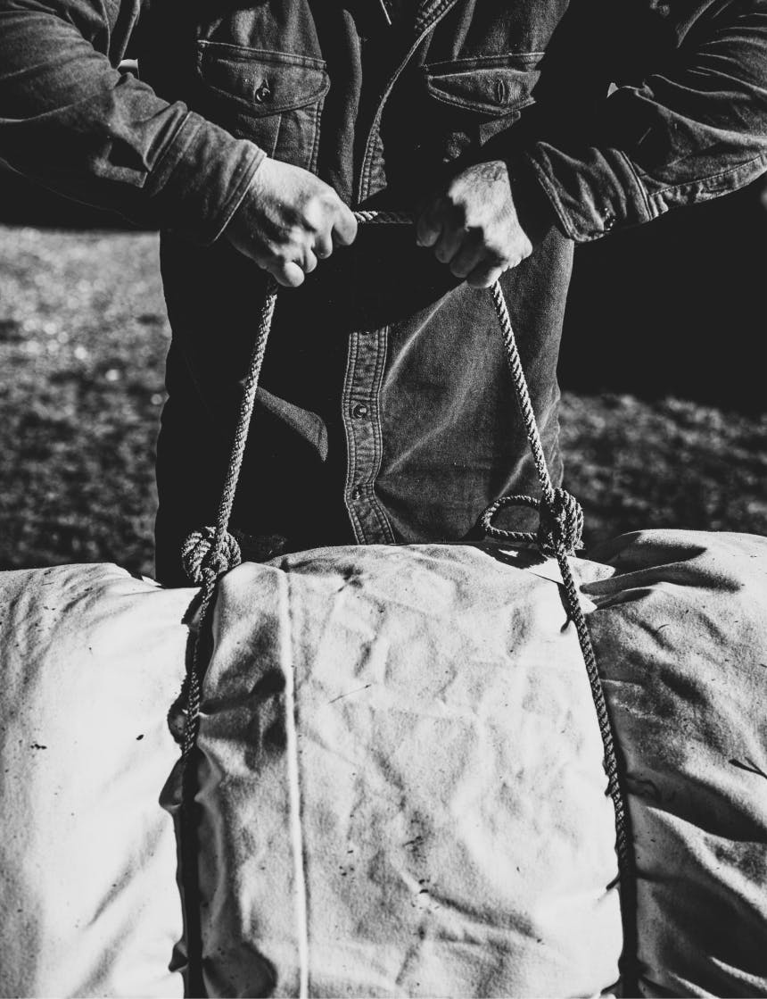 hands holding a bedroll tie containing a canvas bedroll