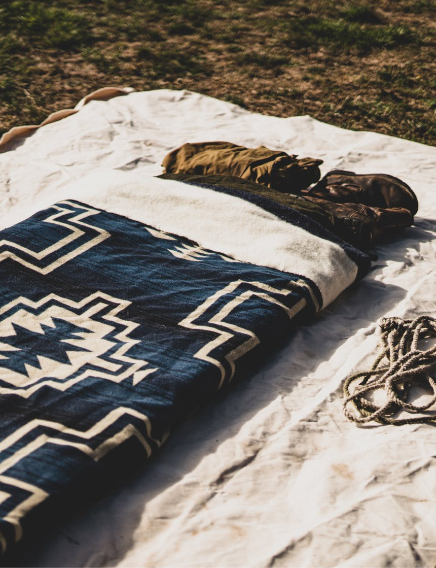 a canvas bedroll with a woven native american style blanket in a grassy field