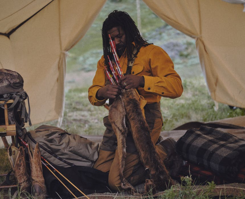 ray livingston with a fur quiver of arrows in a large white tent