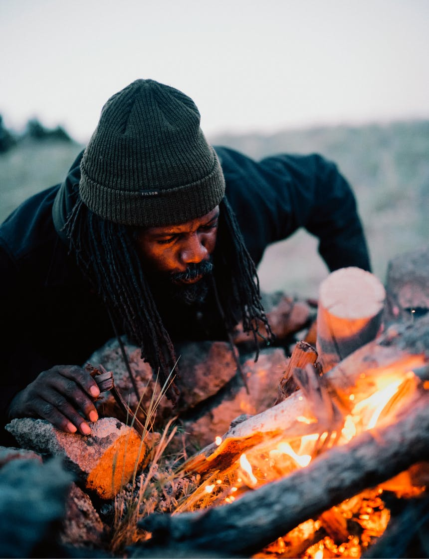 ray livingston stoking coals by blowing on them, wearing a green filson beanie