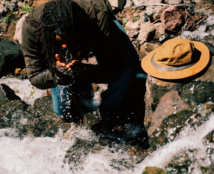 ray livingston splashing stream water on his face as he kneels by running water
