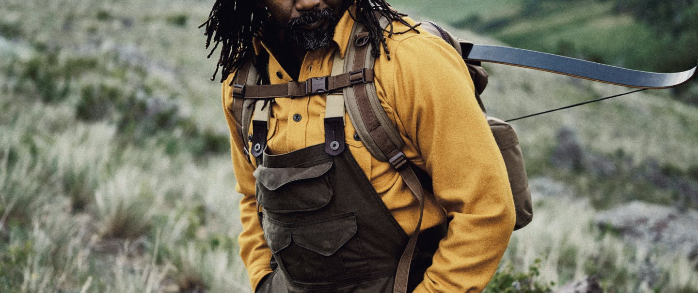 ray livingston in mustard shirt and filson backpack with crossbow on back standing in a mountain meadow