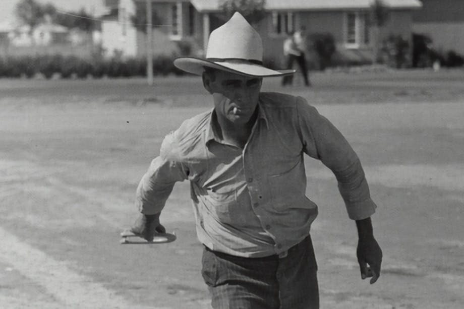 man wearing a white cowboy hat and button up shirt throwing horseshoes in a dirt field