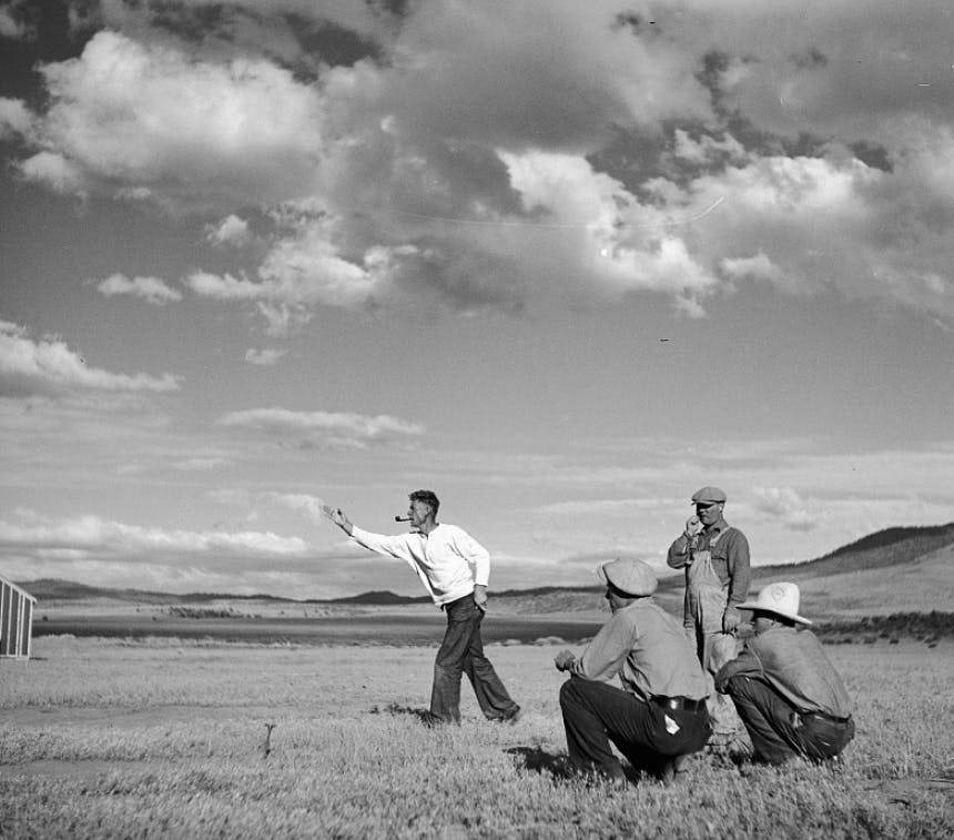 men in a field throwing horseshoes wearing antiquated clothes