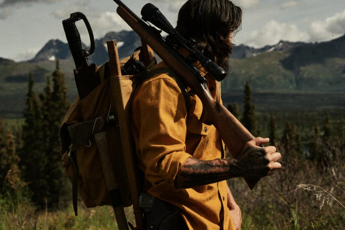 man in mustard colored shirt with gun over shoulder standing in a mountain meadow